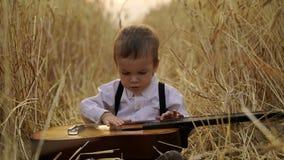 Kleiner Junge, der auf einem goldenen Weizengebiet sitzt und die Gitarre spielt Stockbild