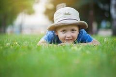 Kleiner Junge, der auf einem grünen Gras im Park liegt Lizenzfreie Stockfotos