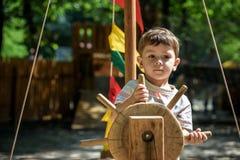 Kleiner Junge, der auf einem hölzernen Spielplatz im Seilpark klettert Warmer sonniger Sommertag des Kinderspiels draußen Lizenzfreie Stockfotografie