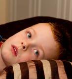 Kleiner Junge, der auf einem Kissen an der Schlafenszeit sich entspannt Lizenzfreies Stockbild
