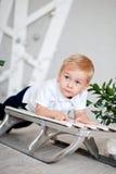 Kleiner Junge, der auf einem Schlitten liegt Lizenzfreie Stockbilder