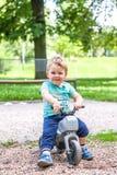 Kleiner Junge, der auf einem Spielzeugmotorrad sitzt Stockfoto