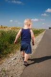Kleiner Junge, der auf einem Straßenrand läuft Lizenzfreie Stockbilder