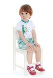 Kleiner Junge, der auf einem Stuhl sitzt stockfotografie