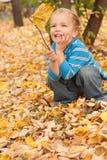 Kleiner Junge, der auf gelbem Herbstlaub sitzt. Stockfotos