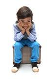 Kleiner Junge, der auf Gepäck sitzt stockfoto