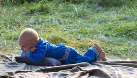 Kleiner Junge, der auf grünem Gras liegt lizenzfreies stockfoto