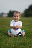 Kleiner Junge, der auf grünem Gras sitzt Stockfoto
