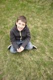 Kleiner Junge, der auf Gras sitzt Stockbild