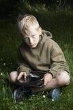 Kleiner Junge, der auf Gras sitzt und Tablet-Computer verwendet Stockfoto