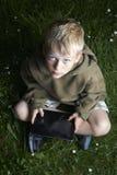Kleiner Junge, der auf Gras sitzt und Tablet-Computer verwendet Lizenzfreies Stockbild