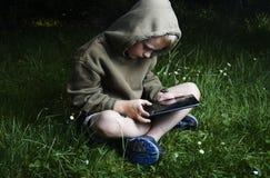 Kleiner Junge, der auf Gras sitzt und Tablet-Computer verwendet Lizenzfreie Stockbilder