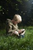 Kleiner Junge, der auf Gras sitzt und Tablet-Computer verwendet Lizenzfreie Stockfotografie