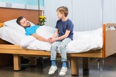 Kleiner Junge, der auf Krankenhausbett sitzt und kranken Vater betrachtet stockfotografie