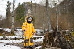 Kleiner Junge, der auf Natur am windigen und kalten Tageswintertag spielt stockfotos
