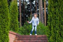 Kleiner Junge, der auf schöner Gartentreppe läuft Lizenzfreies Stockfoto