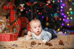 Kleiner Junge, der auf seinem Magen im Raum mit Weihnachtsdekor liegt lizenzfreies stockbild