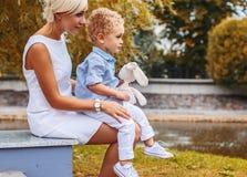 Kleiner Junge, der auf seinen Mutterknien in einem Park sitzt Lizenzfreies Stockfoto