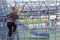 Kleiner Junge, der auf Spielplatz Park des Sommers im im Freien spielt Lizenzfreie Stockfotos