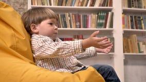 Kleiner Junge, der auf Stuhl und fangendem und werfendem Ball, Bücherregalhintergrund sitzt stock video