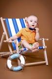 Kleiner Junge, der auf sunbed sitzt Lizenzfreie Stockfotos