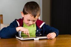 Kleiner Junge, der auf Tablet-Computer spielt Lizenzfreie Stockfotos