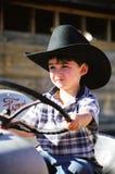Kleiner Junge, der auf Traktor des Großvaters spielt Lizenzfreies Stockbild