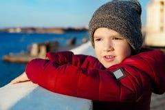 Kleiner Junge, der auf Ufer von See auf großem Stein und von Blicken in Abstand am sonnigen Tag steht Stockfoto