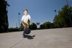 Kleiner Junge, der Basketball spielt Stockbild