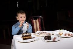 Kleiner Junge, der bei Tisch weg von einer Scheibe des Kuchens beendet Lizenzfreie Stockfotografie