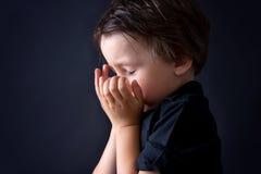 Kleiner Junge, der, betendes Kind, Hintergrund betet stockfotos