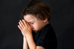Kleiner Junge, der, betendes Kind, lokalisierter Hintergrund betet stockfotos