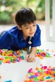 Kleiner Junge, der Blockspielzeug-Innentätigkeiten spielt Lizenzfreie Stockbilder