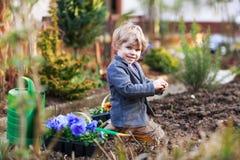 Kleiner Junge, der Blumen im Garten im Garten arbeitet und pflanzt Lizenzfreie Stockbilder