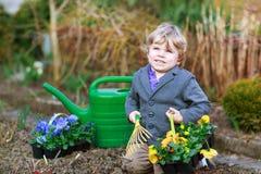 Kleiner Junge, der Blumen im Garten im Garten arbeitet und pflanzt Stockbild