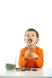 Kleiner Junge, der Bonbons isst volle Schüssel der Süßigkeit Stockbild