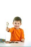 Kleiner Junge, der Bonbons isst volle Schüssel der Süßigkeit Lizenzfreies Stockbild
