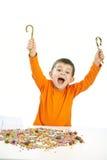 Kleiner Junge, der Bonbons isst volle Schüssel der Süßigkeit Lizenzfreie Stockbilder