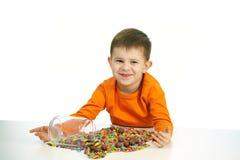 Kleiner Junge, der Bonbons isst volle Schüssel der Süßigkeit Stockfotos