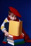 Kleiner Junge in der bunten Kleidung ein Buch lesend Lizenzfreies Stockbild