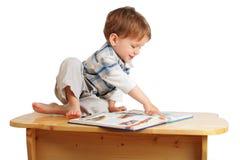 Kleiner Junge, der das Buch auf dem Schreibtisch liest Lizenzfreies Stockbild