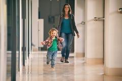 Kleiner Junge, der in das Einkaufszentrum mit seiner Mutter auf Hintergrund läuft Lizenzfreies Stockfoto