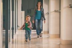 Kleiner Junge, der in das Einkaufszentrum mit seiner Mutter auf Hintergrund läuft Lizenzfreie Stockfotos