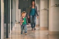 Kleiner Junge, der in das Einkaufszentrum mit seiner Mutter auf Hintergrund läuft Stockfoto