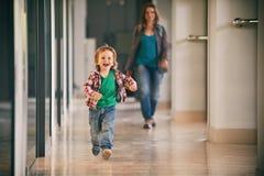 Kleiner Junge, der in das Einkaufszentrum mit seiner Mutter auf Hintergrund läuft Lizenzfreies Stockbild