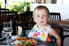 Kleiner Junge, der das Mittagessen isst Stockfotos