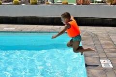 Kleiner Junge, der in das Pool springt lizenzfreie stockfotografie