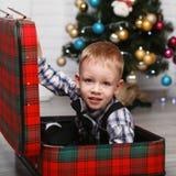 Kleiner Junge, der das Verstecken in einem roten Plaidkoffer im interio spielt Lizenzfreie Stockbilder