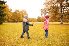 Kleiner Junge, der dem Mädchen Herbstahornblätter gibt Lizenzfreies Stockbild