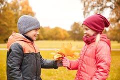 Kleiner Junge, der dem Mädchen Herbstahornblätter gibt Stockfotografie